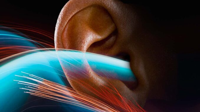 Light trails represent sound waves as they stream into a human ear.