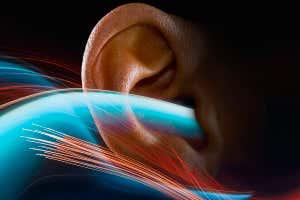 Los senderos de luz representan ondas de sonido a medida que fluyen hacia un oído humano.
