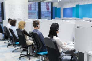 grupo de jóvenes empresarios con auriculares trabajando y ayudando a los clientes en el centro de llamadas; Número de identificación del obturador 703597705; orden de compra: -; trabajo: -; cliente: -; otro: -